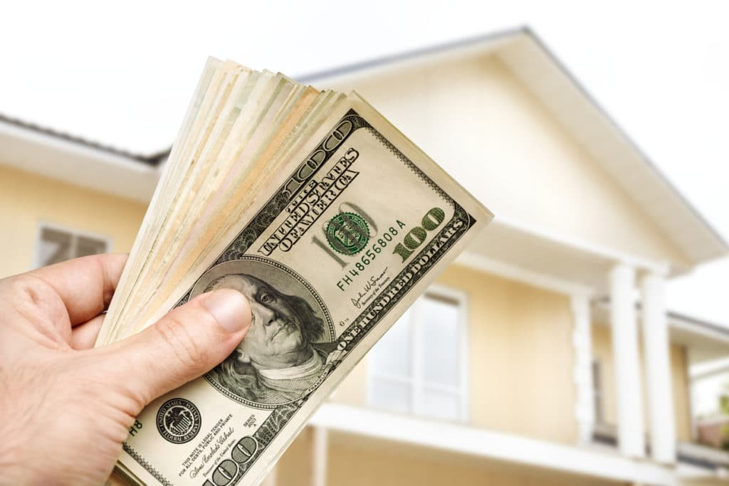 Someone holding money in front of a house from selling to a cash buyer.